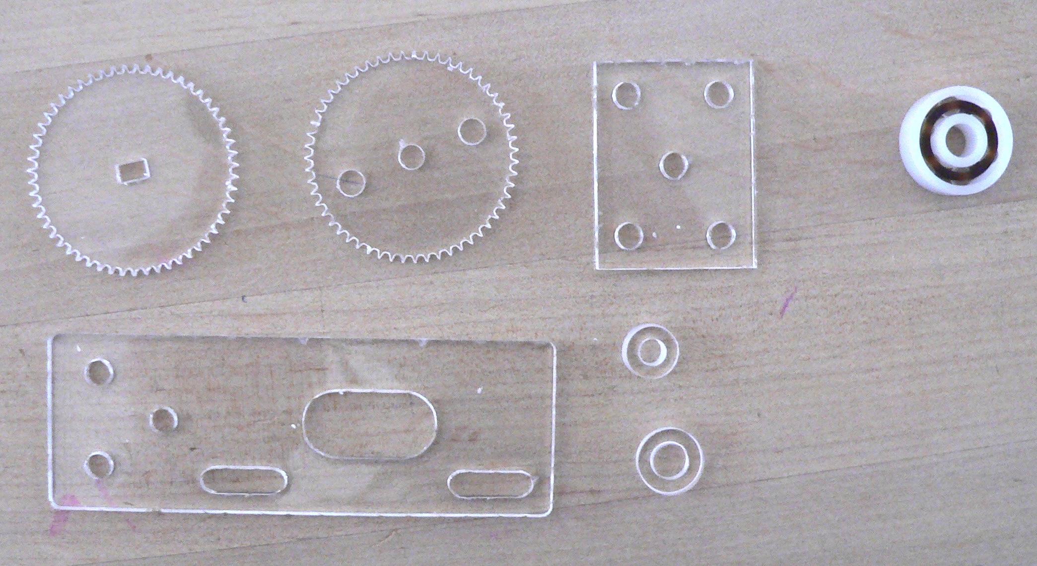 Laser-cut parts: axle bearings, motor mounts, gears, spacers; plastic bearing